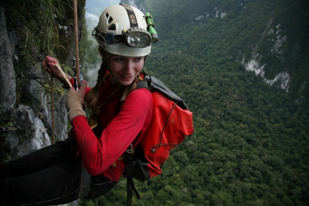 A woman wearing a helmet while rappelling.