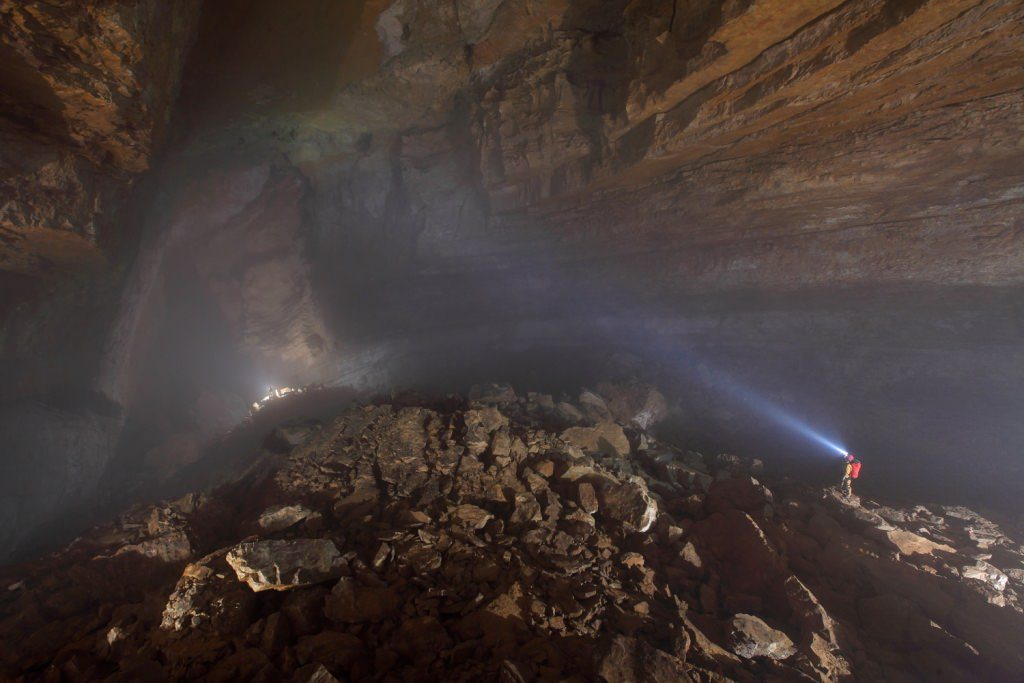 A person with a headlamp lighting up a cave during Greenland caving.