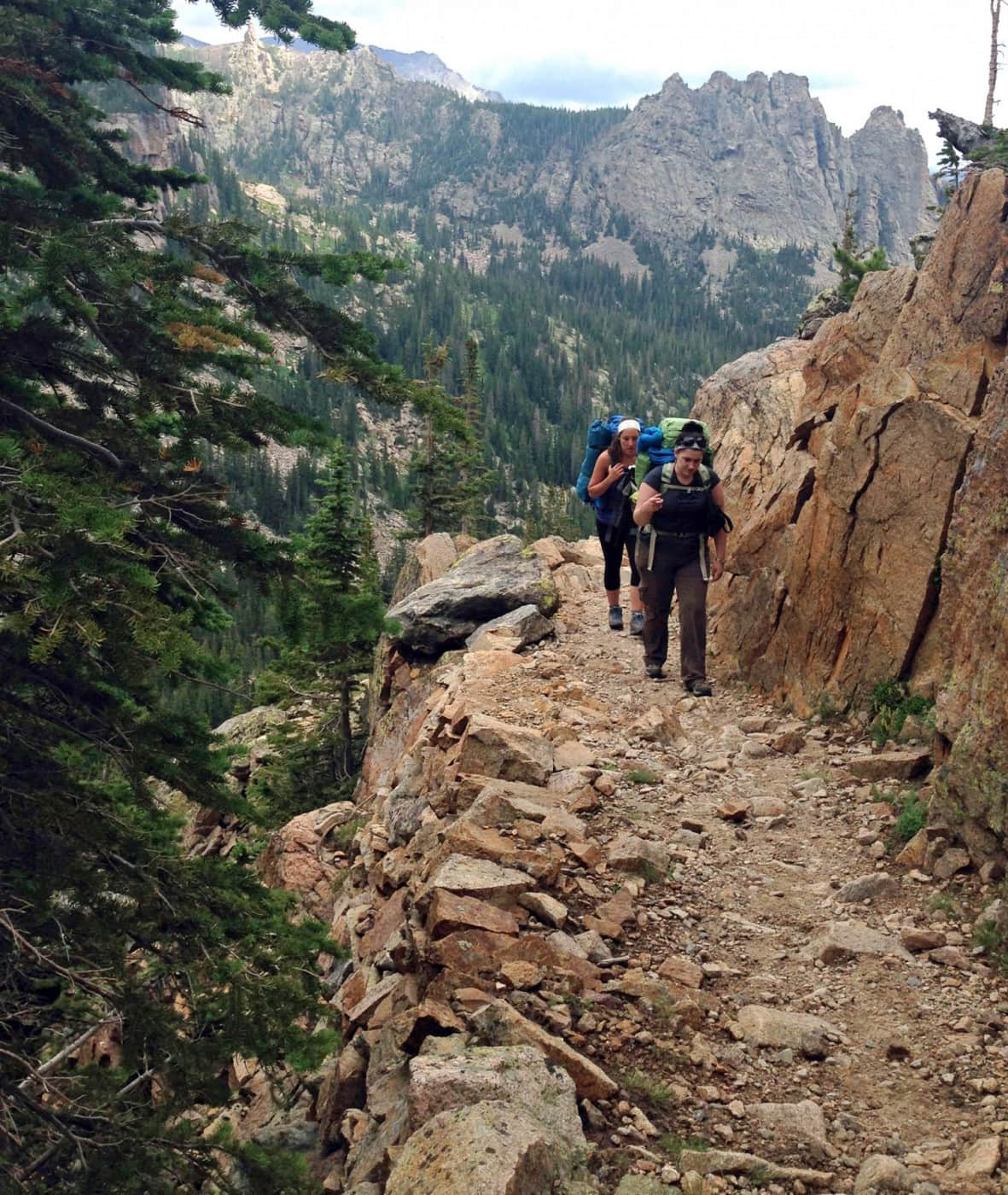 Two women hike with backpacks along a rocky trail