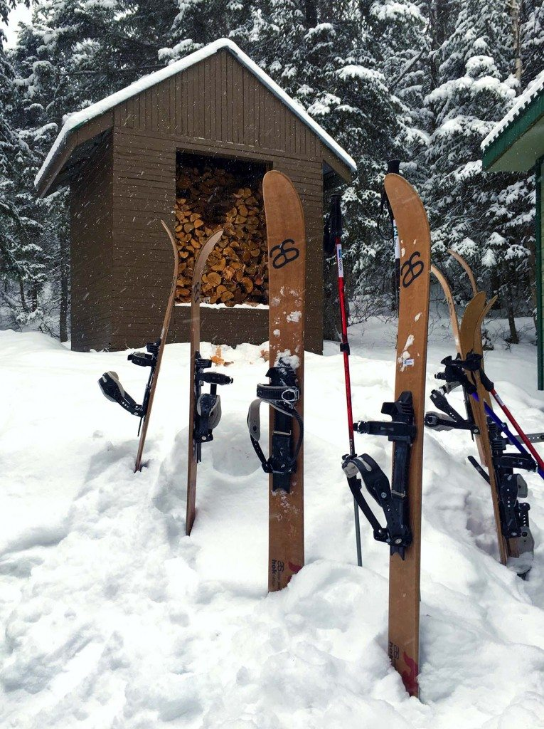 Skis propped up in the snow outside a ski hut.