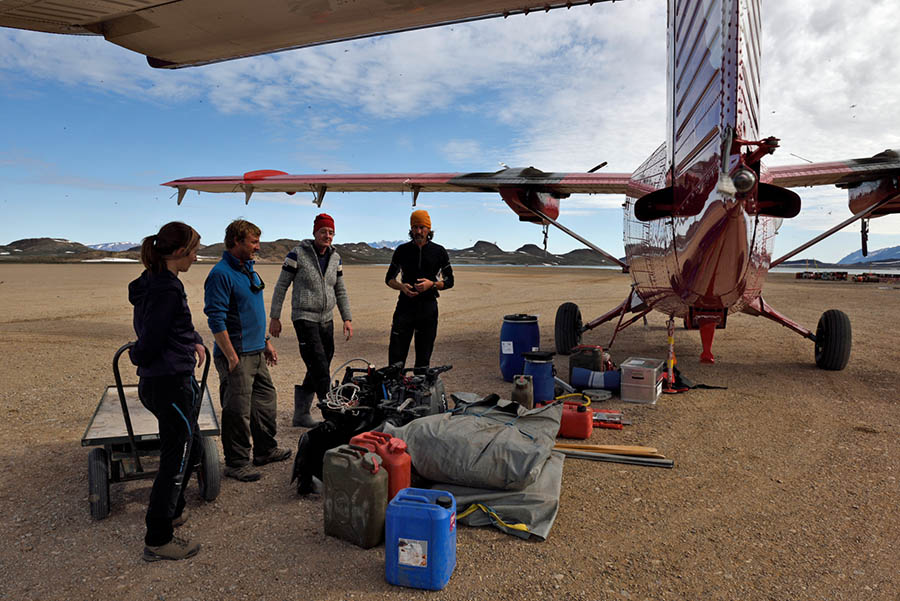 Group of four people standing with gear besides a plane for their trip to Greenland caves.