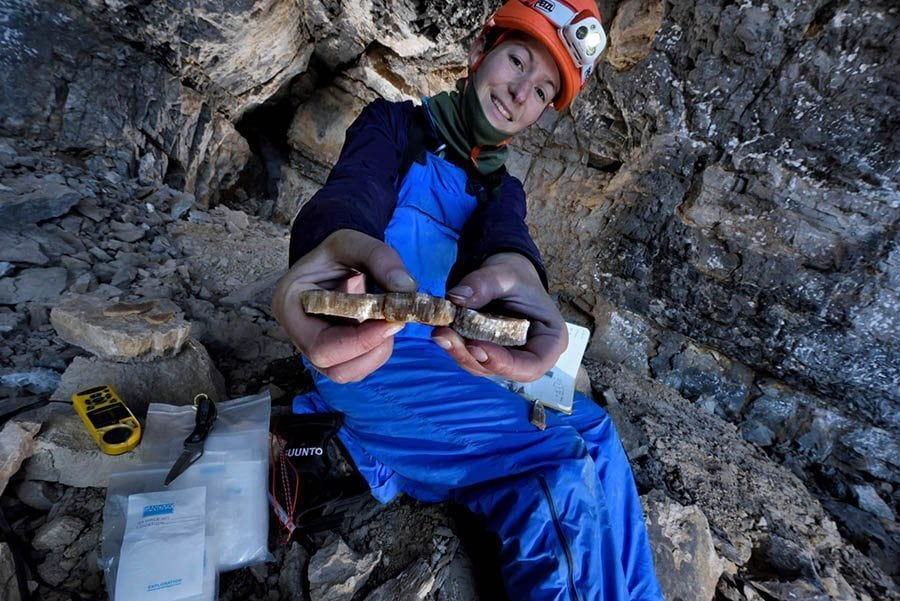A woman showing a sample of rock.