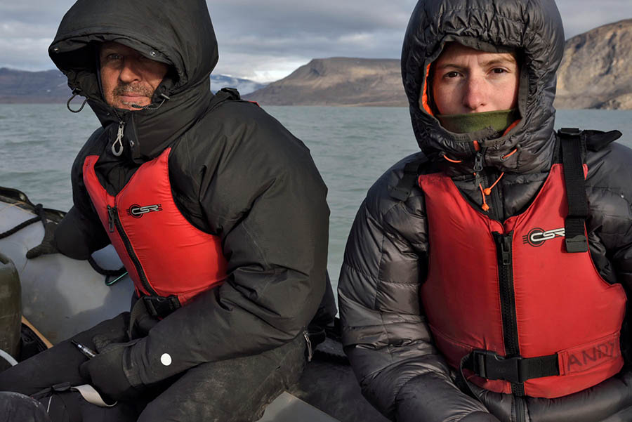 Man and woman wearing black jackets with hoods up and life jackets.