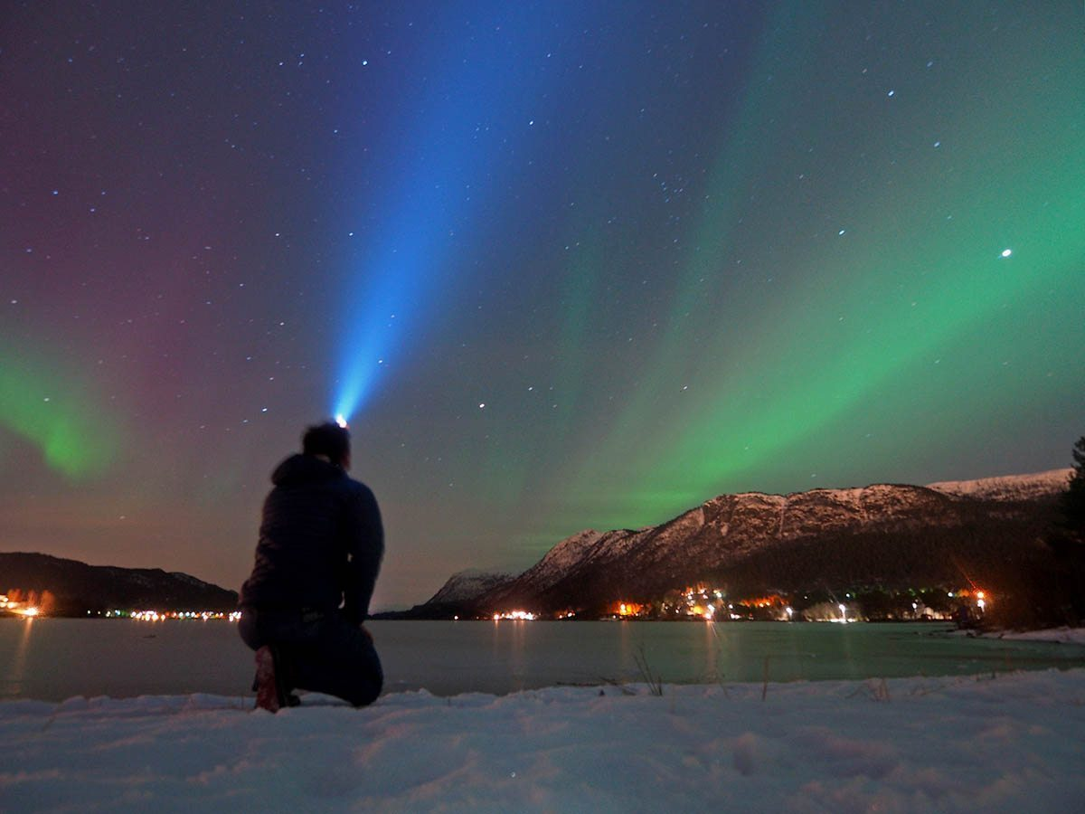 A person wearing a headlamp admiring the Northern Lights.