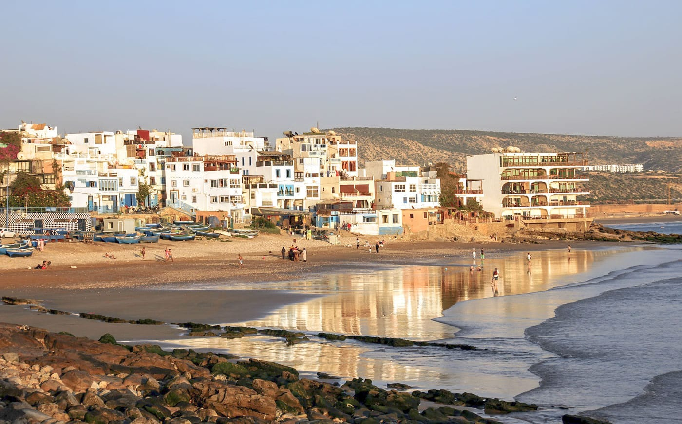 People on a beach in Taghazout, Morocco with buildings in the background.