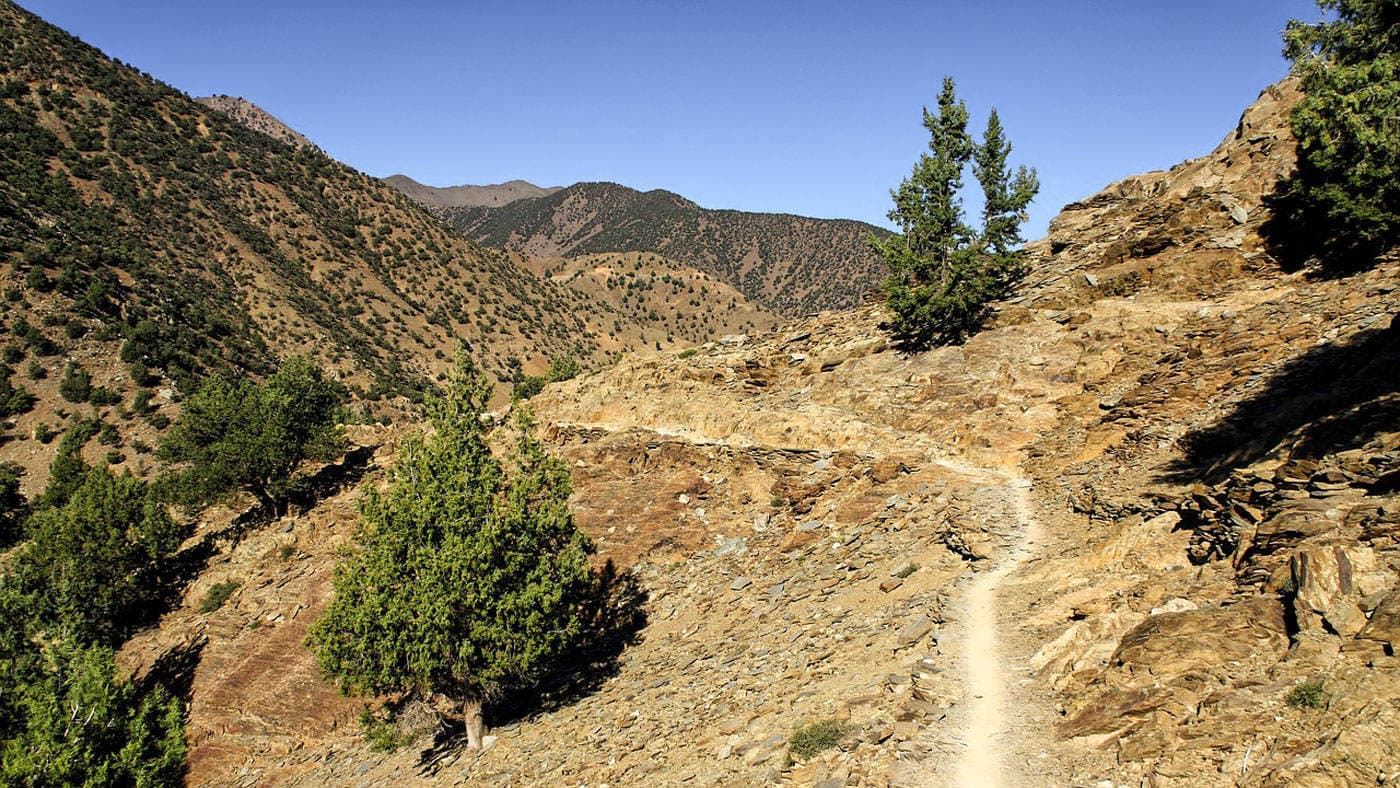 A mountain biking trail in the Atlas Mountains, desert and hills with some greenery.