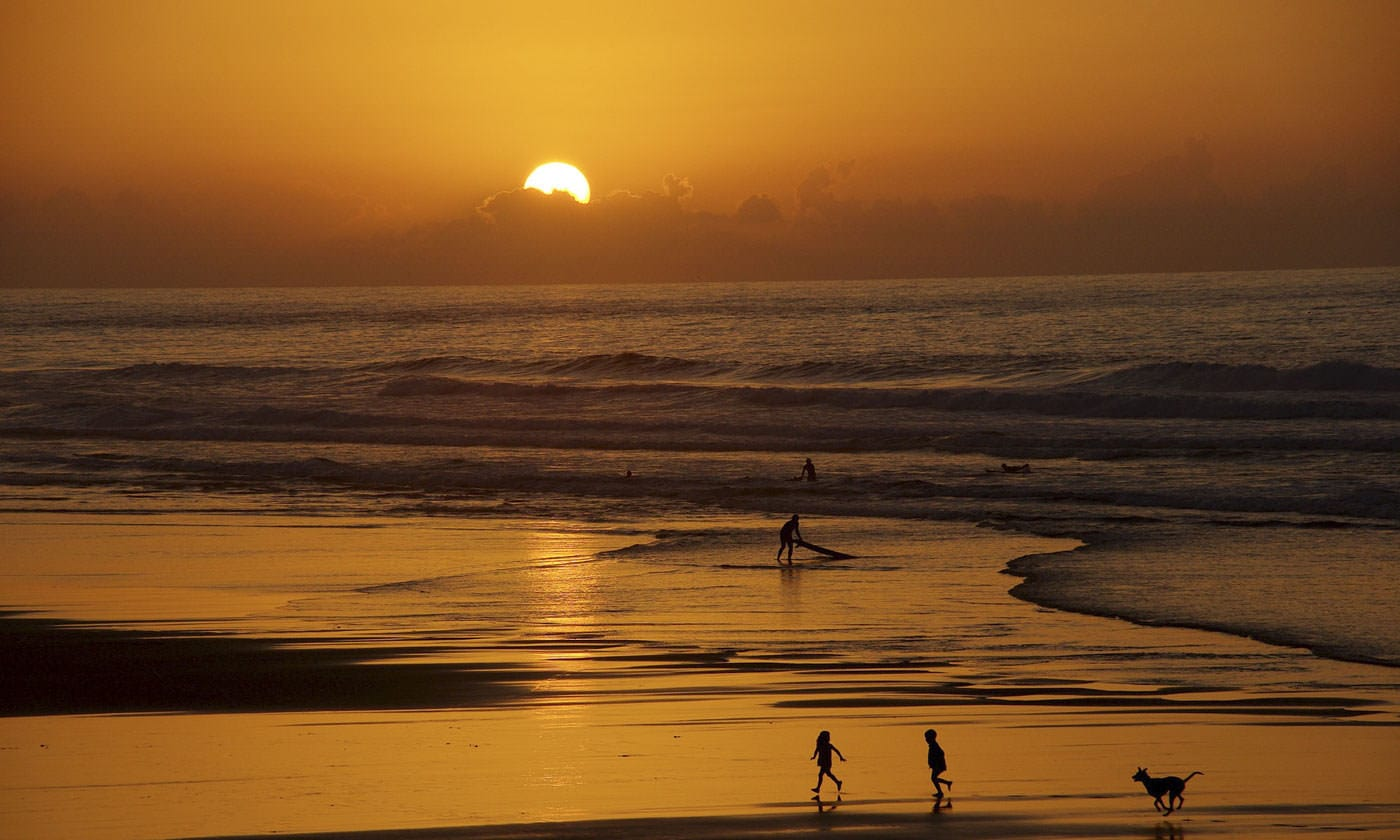 Silhouettes of people playing on the beach and surfing as the sun sets.