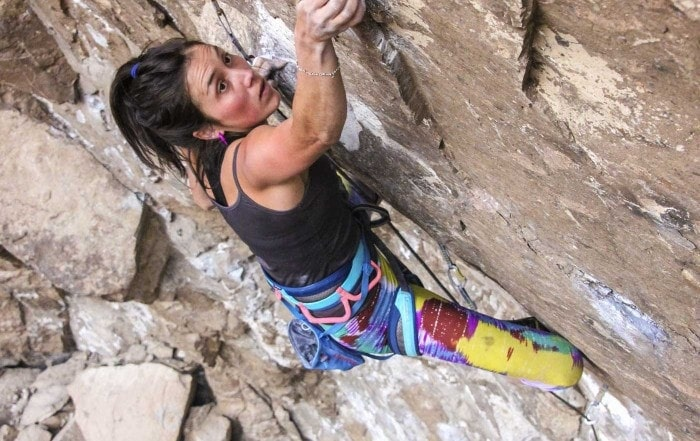 Woman moves above the clip, grabbing the hold, while lead climbing in Piedra Parada, a climbing area in Argentina's Patagonia region