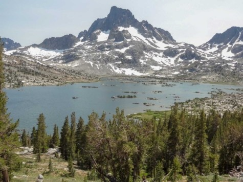 Lake view with trees in the foreground and snowy sharp mountains in the background, part of the John Muir Trail