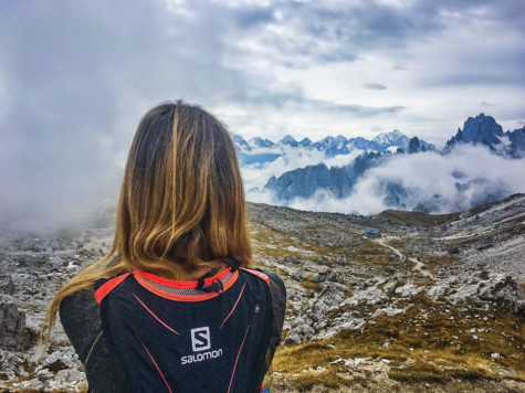 Mental health and adventure: A woman wearing a Salomon running vest looks out over snowy mountains.