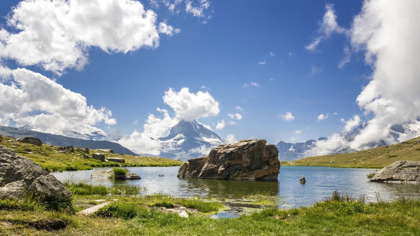 A pond reflecting the sky in a mountain meadow by the Matterhorn.