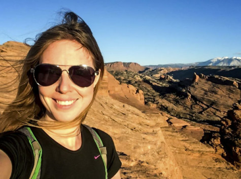 A woman wearing sunglasses standing on red rock.