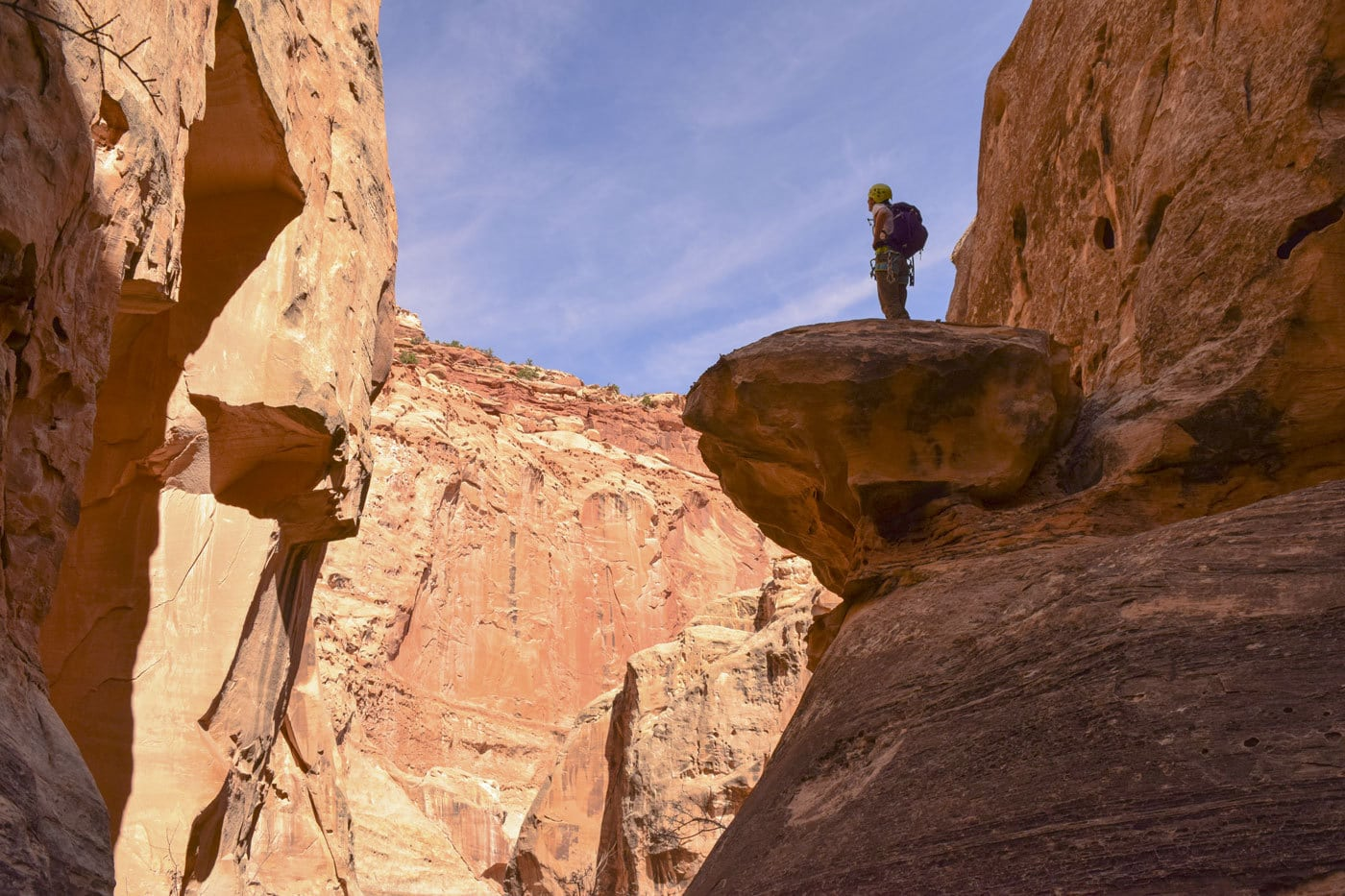 A person stands on a ledge in Cassidy Arch Canyon in Capitol Reef National Park.