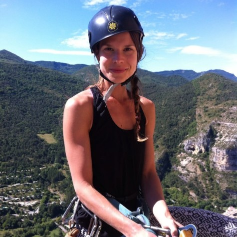 Roanne Van Voorst: a woman wearing climbing gear at the top of a climb.