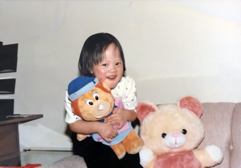 Lynn as a young girl holding a stuffed animal