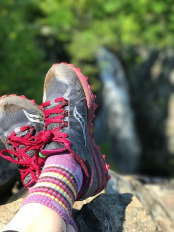 A person with Saucony shoes in focus with a waterfall out of focus in the background.