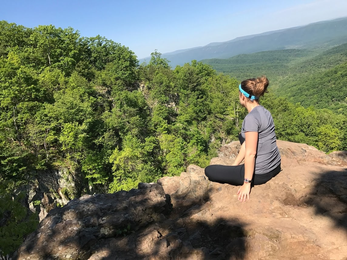 A woman sitting on a rock overlooking the green Shenandoah Valley