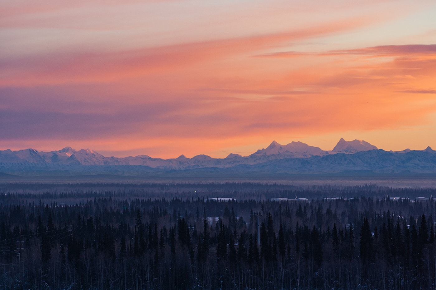Orange sky and clouds with purple mountains in the background in Alaska.