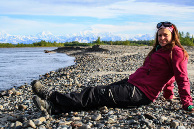 A woman sitting on rocky beach next to water in Alaska.
